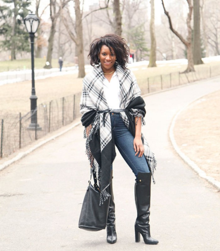 over the knee, black leather boots, over skinny jeans, combined with a whote blouse, and a two-tone grey oversized scarf, worn like a cardigan, scarf outfits, on a smiling black woman