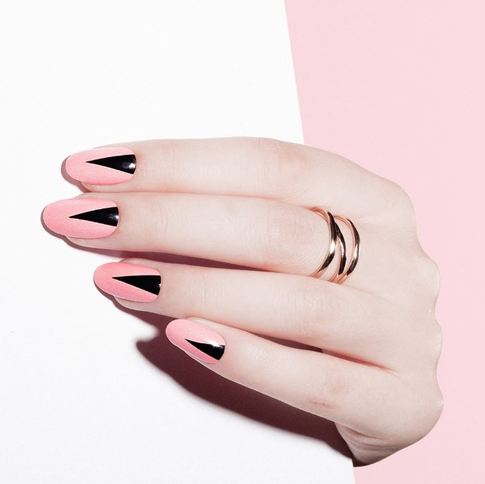 candy pink manicure, decorated with black triangles, on a pale hand, wearing a golden ring, almond shaped nails