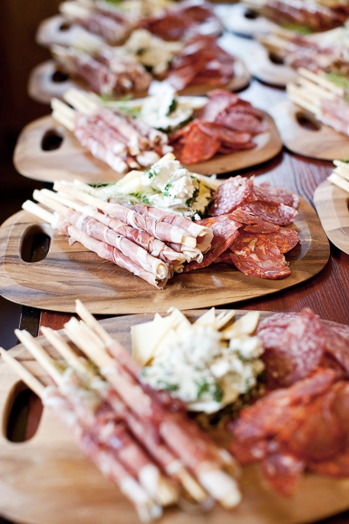 horderves, wooden platters with a selection of salami, cheeses and bread sticks with prosciutto, placed on a table