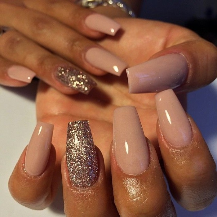 smoky pastel pink nail polish, on coffin shaped manicure, decorated with rose gold glitter, nude gel nails, on two brown hands