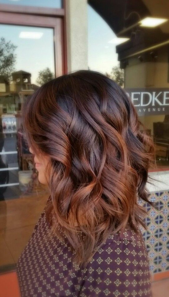 curled shoulder-length hair, with redish-brown highlights, balayage dark hair, on a woman in a patterned top