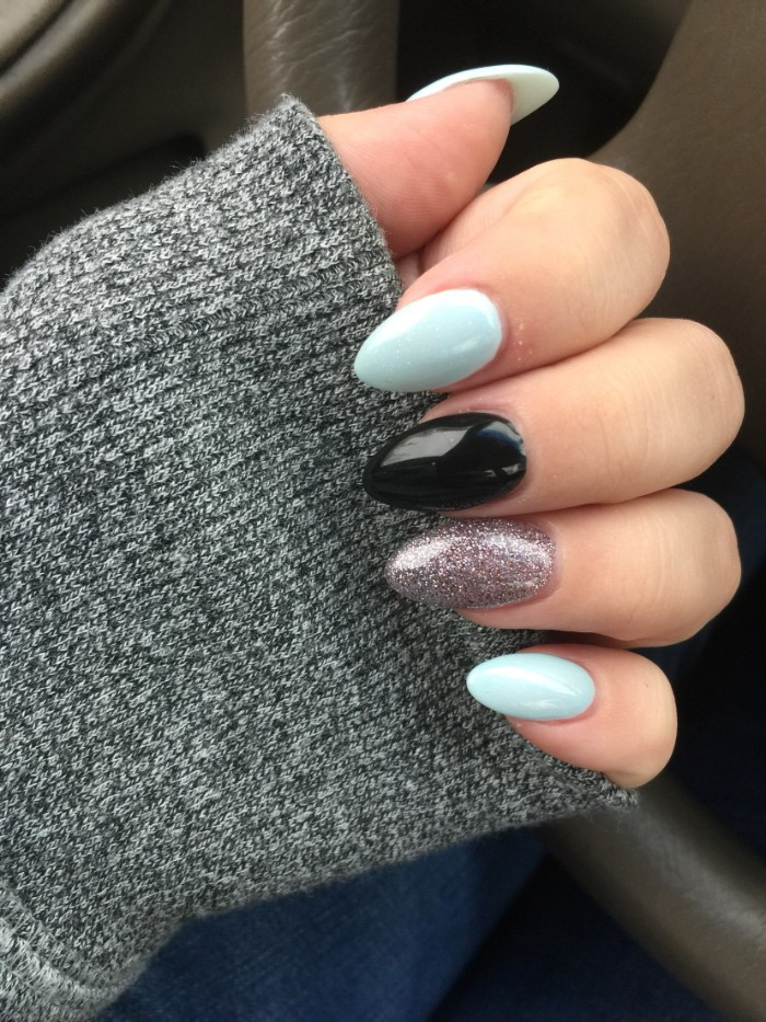 short stiletto nails, in pale blue, black and silver glitter, worn by a pale hand, dressed in a grey sleeve