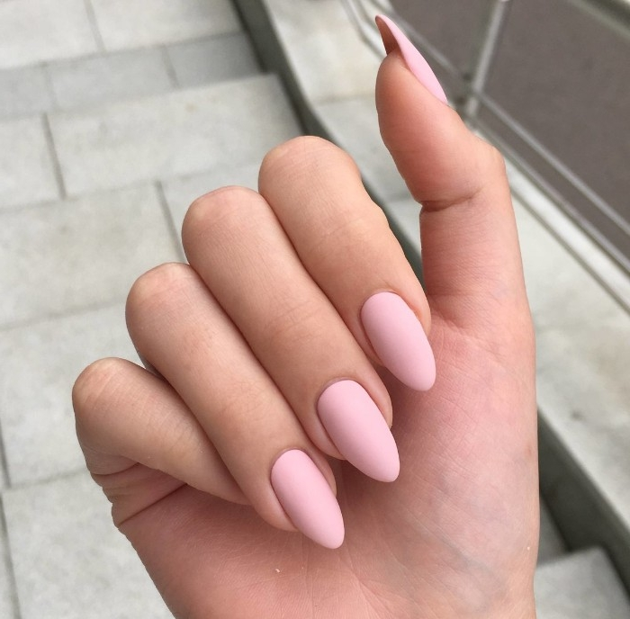 hand with folded fingers, seen in close up, with pastel pink, matte nude nails, pointy oval shape
