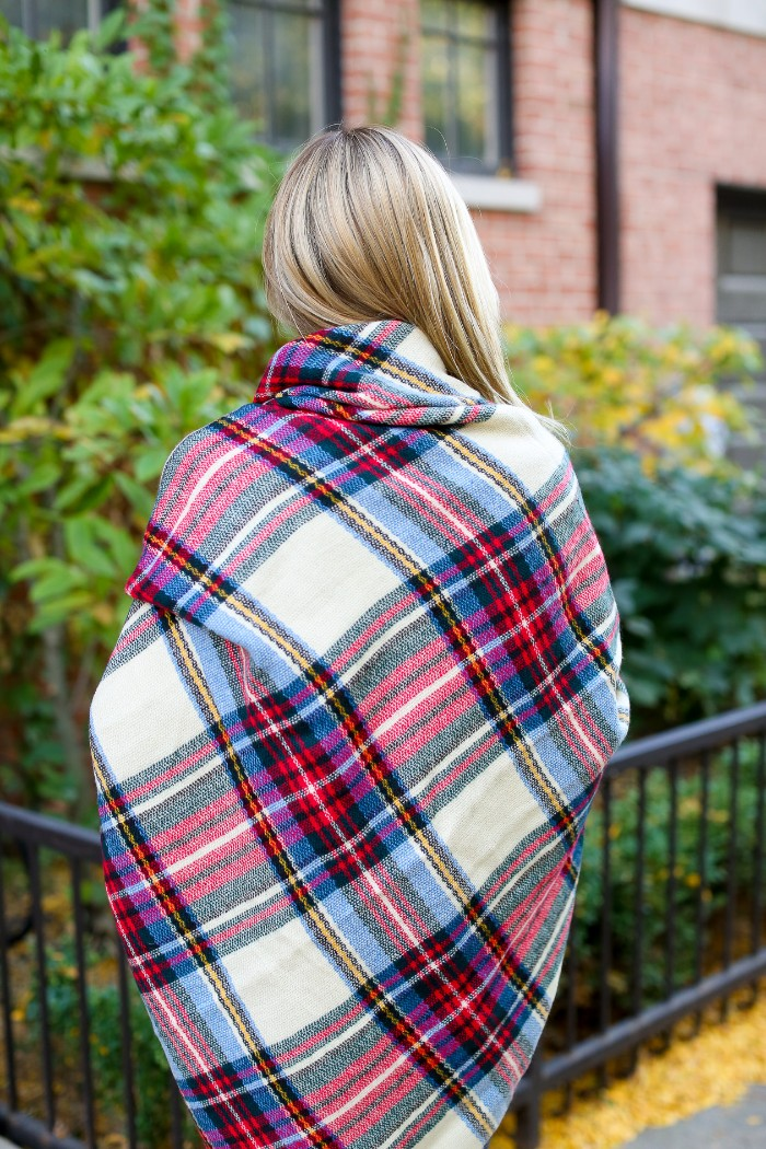 view from the back, showing a blonde woman, wrapped in a large white and red, black and blue tartan scarf, how to wear a blanket scarf, around the shoulders