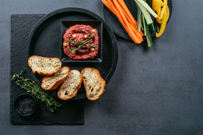 black plate with bruschetta slices, beet hummus in a black bowl on the plate, beet hummus recipe