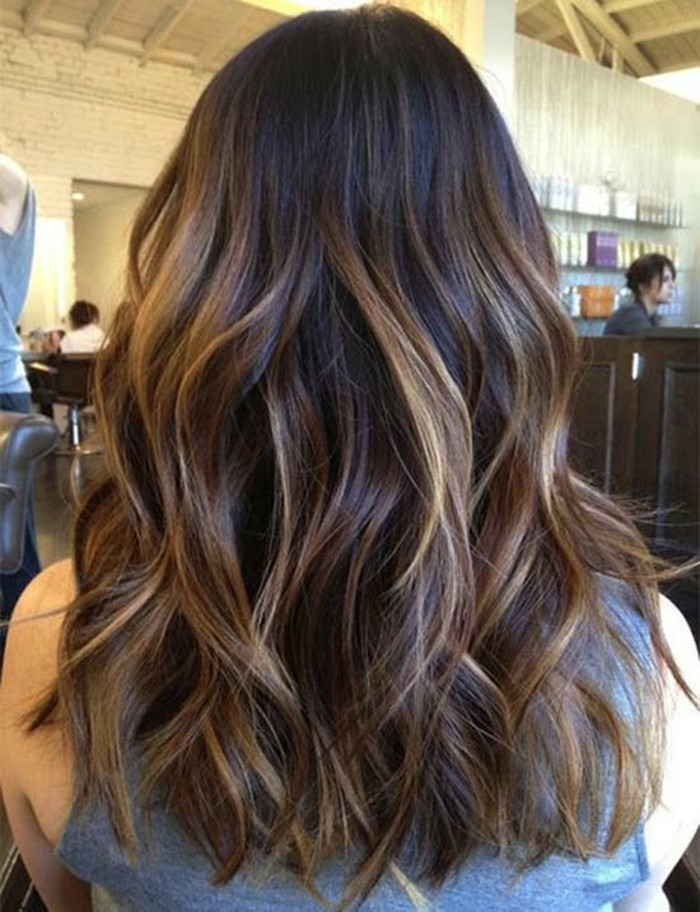 grey sleeveless top, worn by a woman, brown hair with blonde highlights, styled in loose waves, seen from the back