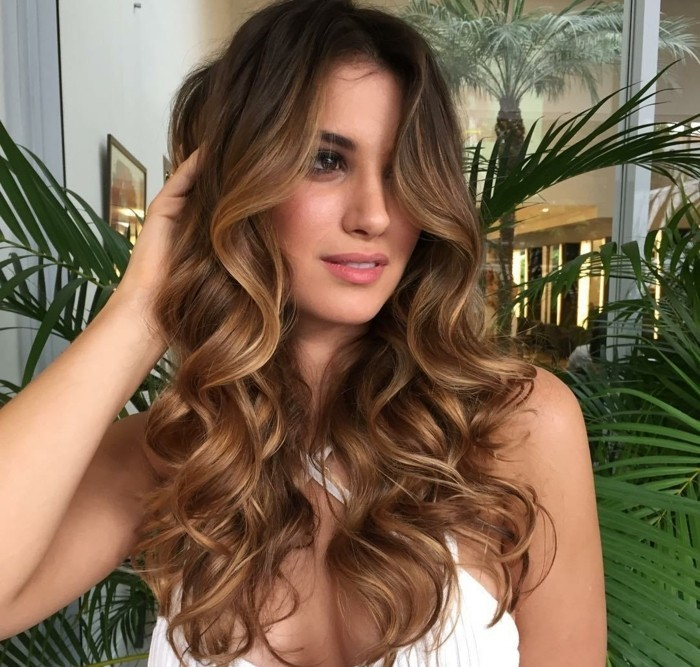 long brunette hair with subtle, natural-looking caramel highlights, and loose curls, worn by a slim young woman, in a white top, balayage dark hair