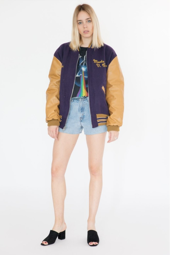 tall young blonde woman, dressed in a vintage patterned t-shirt, and pale denim shorts, 80s fashion trends, navy blue and mustard yellow baseball jacket