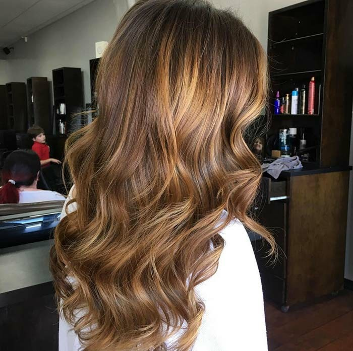 back view of a long, light brunette hairstyle, with a honey blonde balayage, on a woman dressed in white