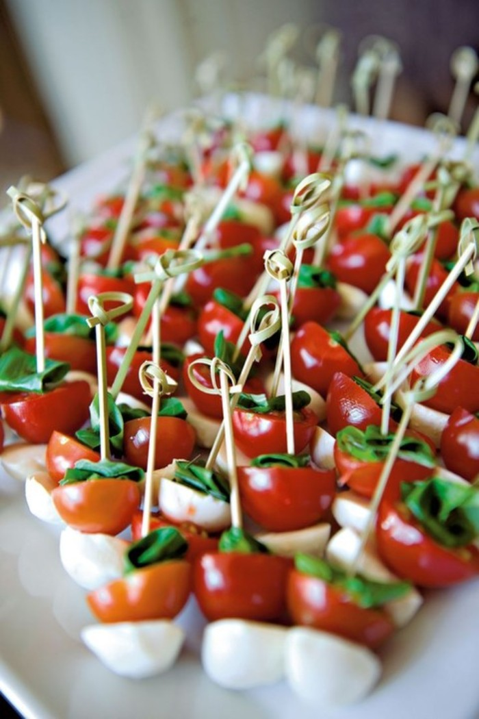 many small skewers, with mozzarella and cherry tomatoes, and fresh basil leaves, served on a large white plate