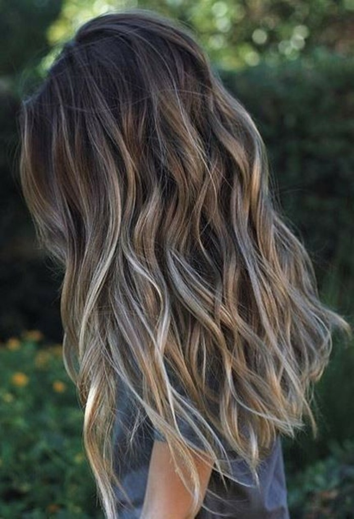 balayage hair, long and wavy, with dark roots, and light blonde highlights, on a woman, dressed in a grey t-shirt