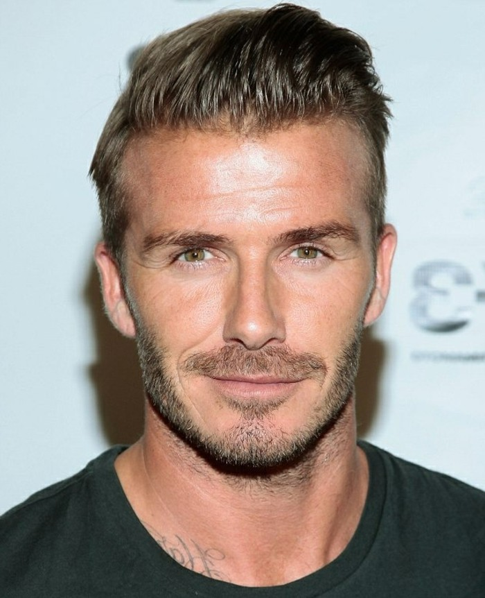 another photo of david beckham, with short slicked, back brunette hair, trendy haircuts for men, smiling in a black t-shirt