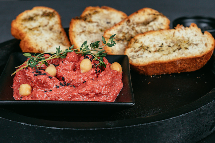 beet hummus recipe, beet hummus in black bowl, garnished with chickpeas and herbs, bruschetta slices on the side
