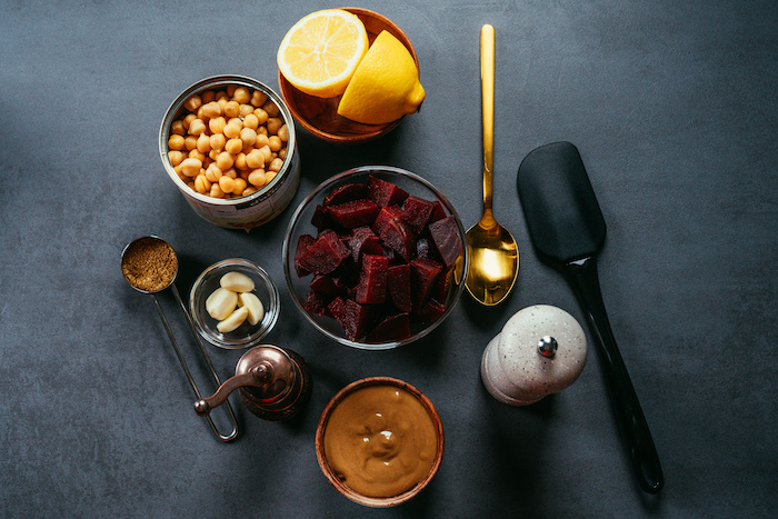 necessary ingredients, beet hummus recipe, arranged in different bowls, placed on black surface
