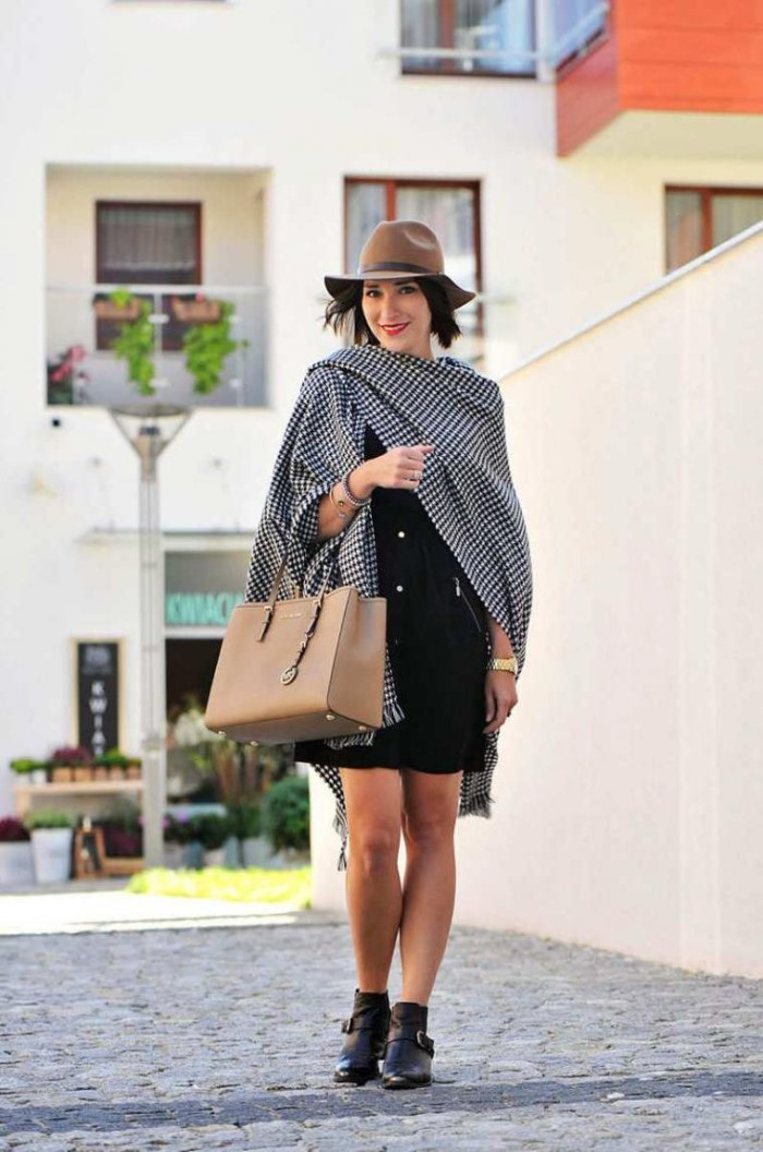 checkered black and white blanket shawl, wrapped arounf the shoulders of a smiling woman, dressed in a black mini dress, accessorized with a beige felt hat, large beige leather bag, and black ankle boots