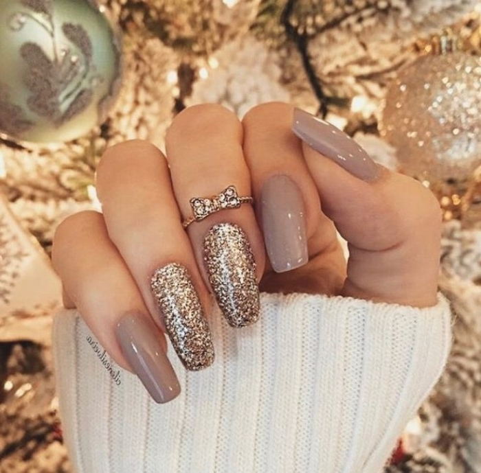 bow-like diamante detail, on a ring, worn by a hand with long, coffin-shaped nails, painted in dark milky grey nail polish, and decorated with gold glitter