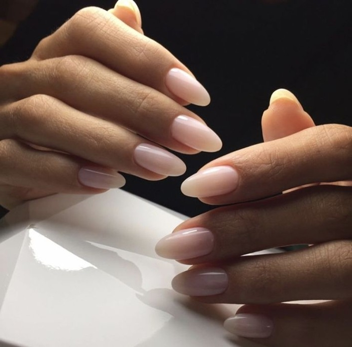 slender fingers on two hands, with oval manicure, painted in nude pink nail polish, in a milky hue