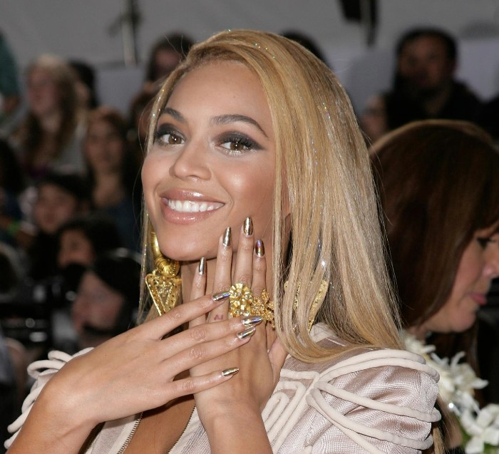 smiling beyonce with smooth blonde hair, bold dark eye make up, and almond shaped nails, painted in a silver shade