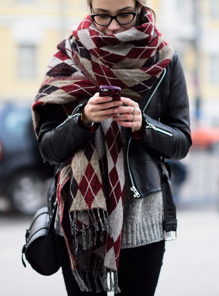 bulky patterned scarf, worn around the neck of a young girl, in a black leather biker jacket, black trousers and a pale grey knitted sweater, scarf outfits for every day wear
