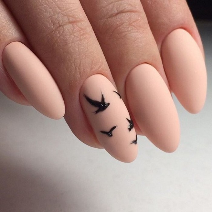 tiny bird-shaped motifs in black, on nude peach pink matte stiletto nails, seen in extreme close up