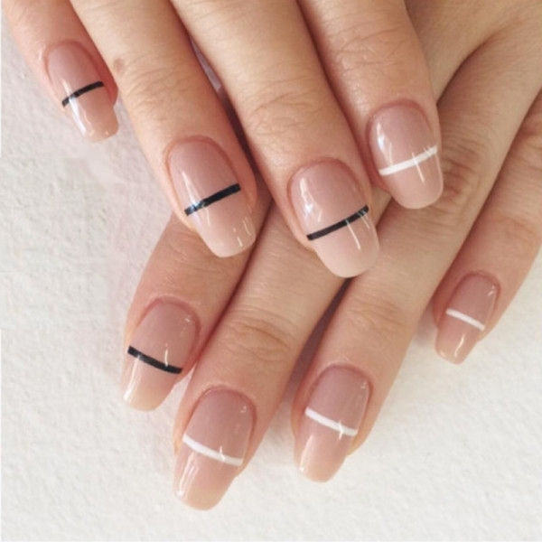 pink nude nails, with an oval shape, each decorated with a white, or a black stripe