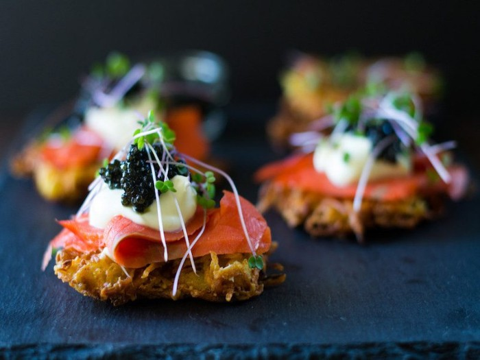 crispy crackers topped with smoked salmon fillets, mayo and black caviar, hors dourves with watercress on top