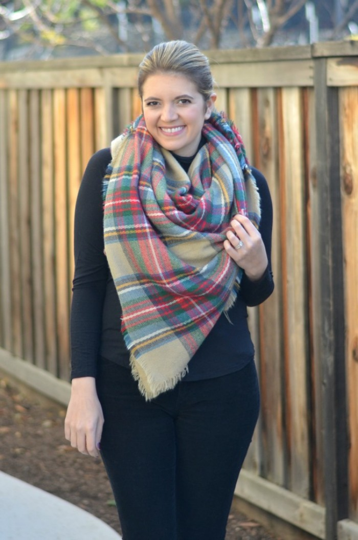jeans and sweater in black, worn by a smilling blonde woman, with hair tied back, oversized beige scarf with tartan print, wrapped around her neck