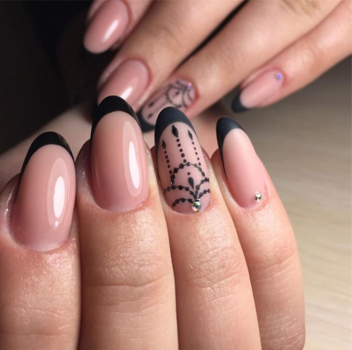 hands with almond shaped nails, in nude pink color, with black tips, and black hand-painted motifs, decorated with rhinestones, some are glossy, while others are matte
