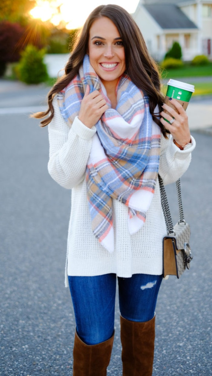 how to fold a blanket scarf, demonstrated by a smiling, slim brunette woman, in a white knitte jumper, distressed skinny jeans, and brown suede, over the knee boots