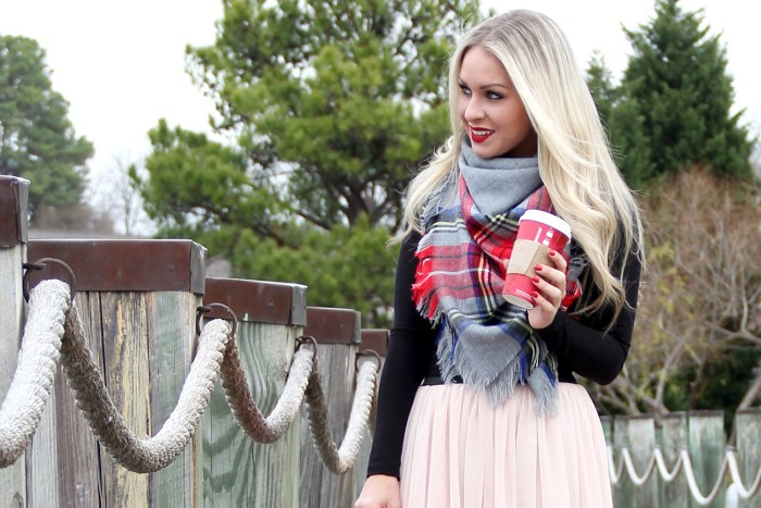 platinum blonde smling woman, holding a red paper coffee cup, dressed in pale pink tulle skirt, black top and a large scarf, how to tie a blanket scarf in fall