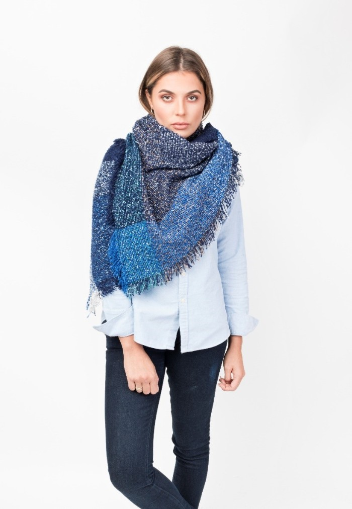 navy and bright blue oversized shaw, wrapped around the shulders of a slim, young brunette woman, how to wear a square scarf, with jeans and a pale shirt