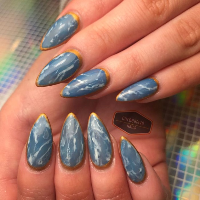manicure in blue, with a marble-like white pattern, and a gold outline, almond nail designs, on two hands