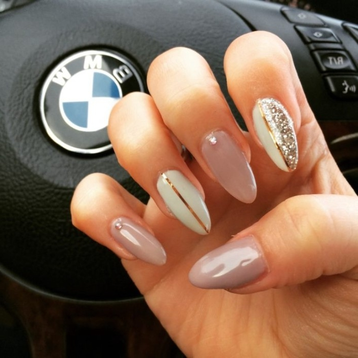 steering wheel of a bmw, behind a hand with folded fingers, and long and pointy, ash pink nude gel nails, decorated with white, silver glitter and metallic gold motifs
