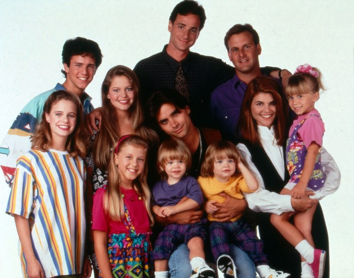 entire cast of the sitcom full house, dressed in vintage outfits, oversized colorful clothes, vests and bold patterns, 80s costumes men and women, bob saget and the olsen twins