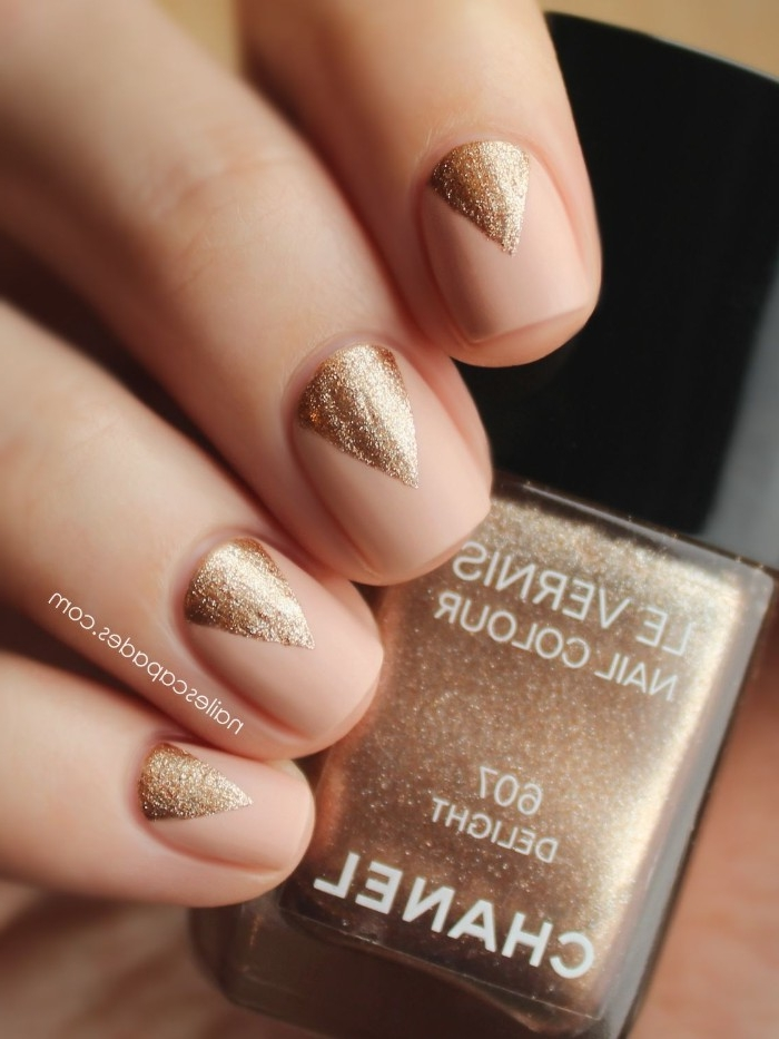 triangles painted in sparkly rose gold, on top of four nails, with nude pink nail polish, on a hand, holding a bottle of rose gold nail polish