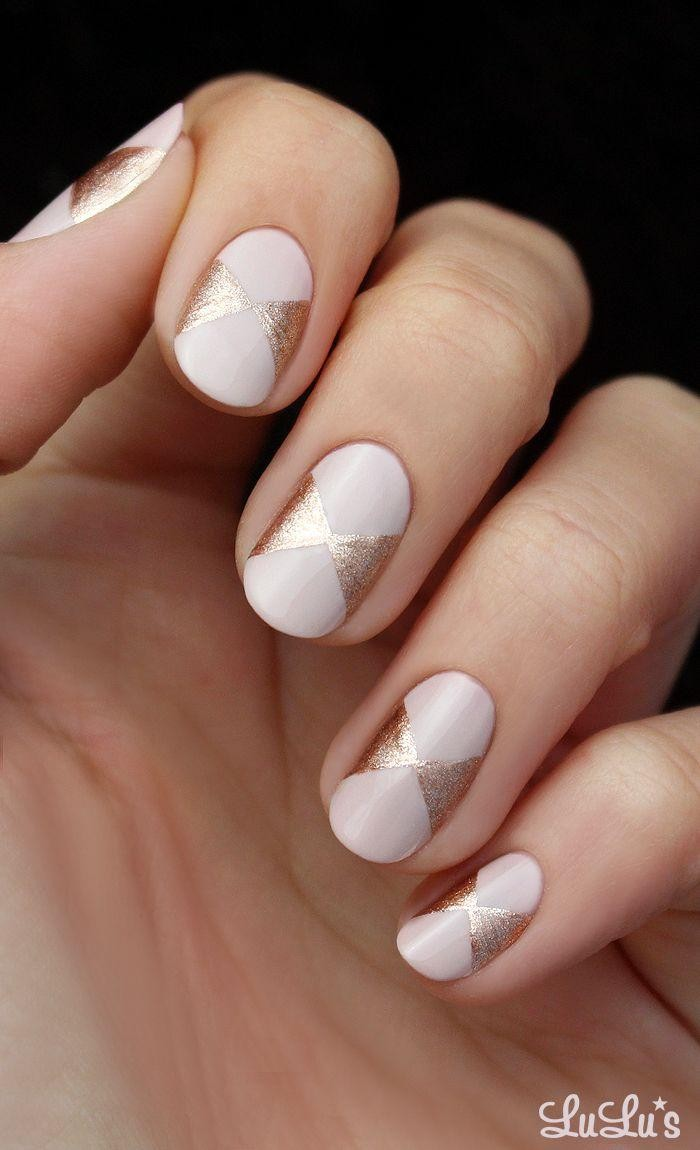 milky pink nude nails, decorated with bow-like motifs, drawn in sparkly rose gold, on a pale hand with folded fingers