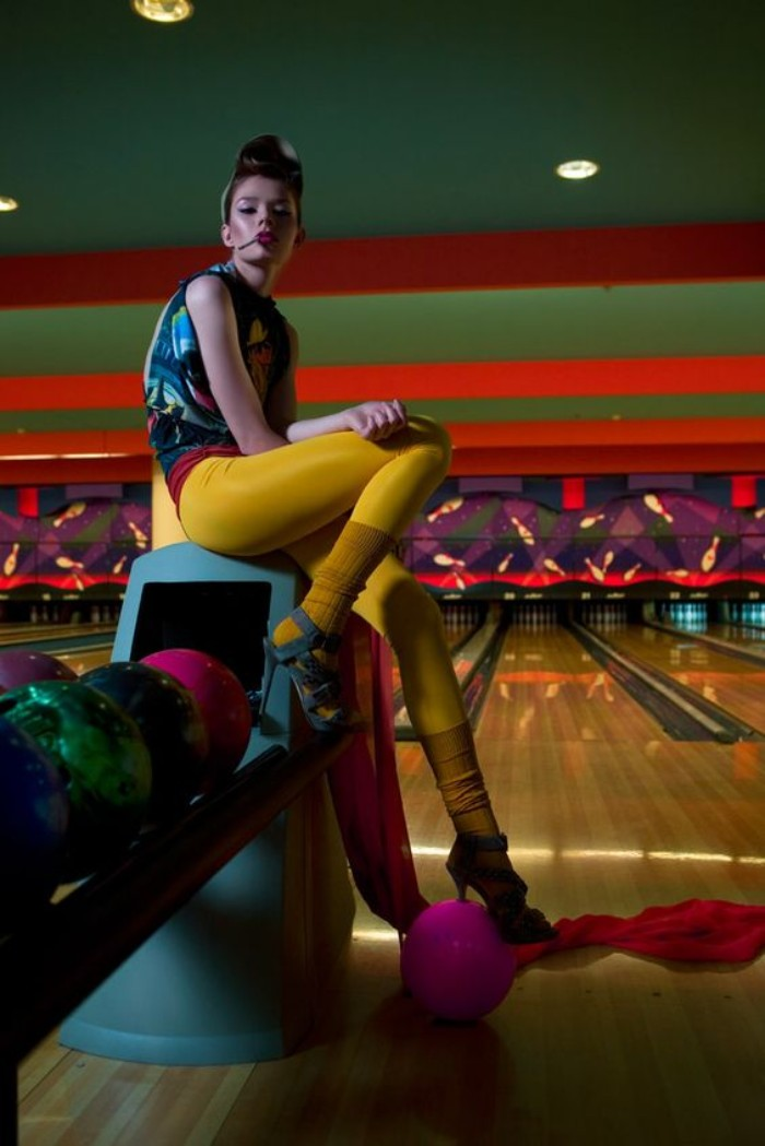 yellow leggings and matching yellow leg warmers, worn with teal high heeled sandals, 80s outfits, by a young woman in a bowling alley
