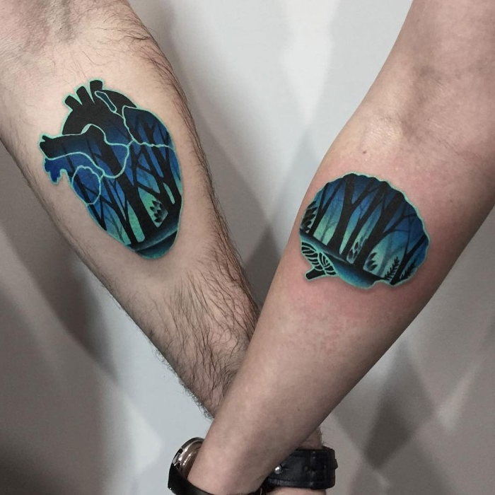 matching tattoos, featuring a brain and a heart shape, decorated with woodland scenery, in dark blue and black, on the lower arms of a couple