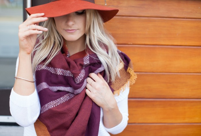 purple shawl in two shades, featuring pale grey details, worn by a blonde woman, wth a large brick red felt hat, how to tie a blanket scarf, around your neck and shoulders