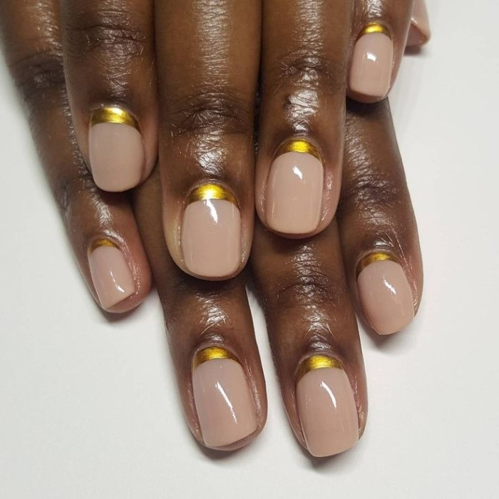 gold metallic details, at the base of nude nails, attached to two dark brown hands, one placed on top of the other