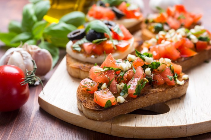 classic bruschetta with chopped tomato, mozzarella and paisley, garlic and olives, hor dourves on a wooden board