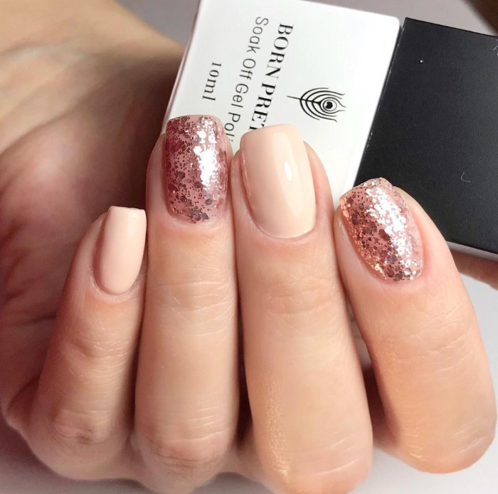 rose gold glitter flakes, on two of the four visible fingers, of a hand with nude nails, holding a business card