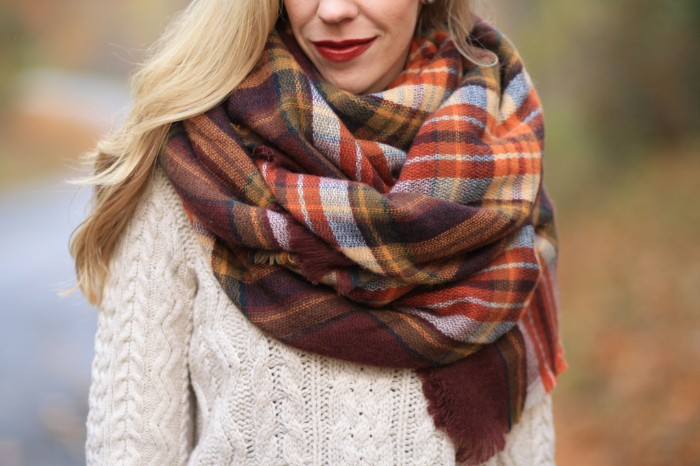 shawl in warm earth tones, wrapped around the neck of a blonde woman, how to tie a blanket scarf, wearing an off-white, cable knit jumper, and dark red lipstick