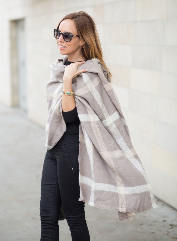 oversized pale grey shawl, with off-white striped pattern, worn by a woman dressed in black, how to tie a blanket scarf