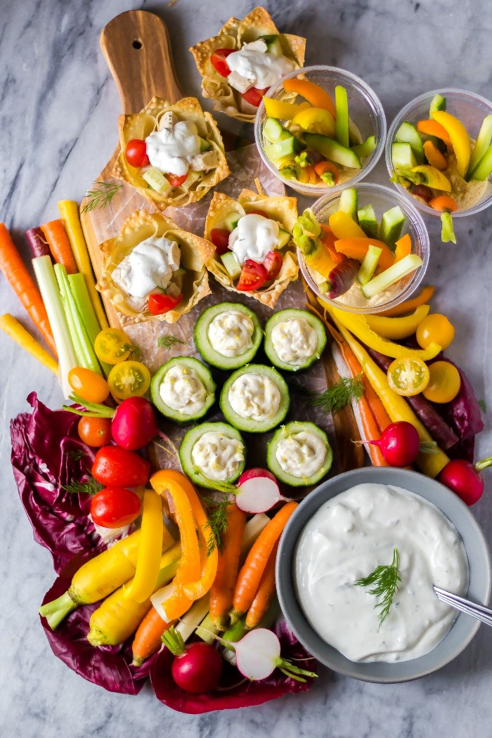 hors d oeuvres recipes, a rich selection of vegetable appetizers, cucumber slices with yoghurt sauce, chopped carrots and celery, cherry tomatoes and radishes