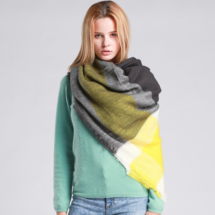 young woman in a duck's egg blue jumper, and acid wash jeans, wearing a blanket shawl, in dark and light grey, white and yellow