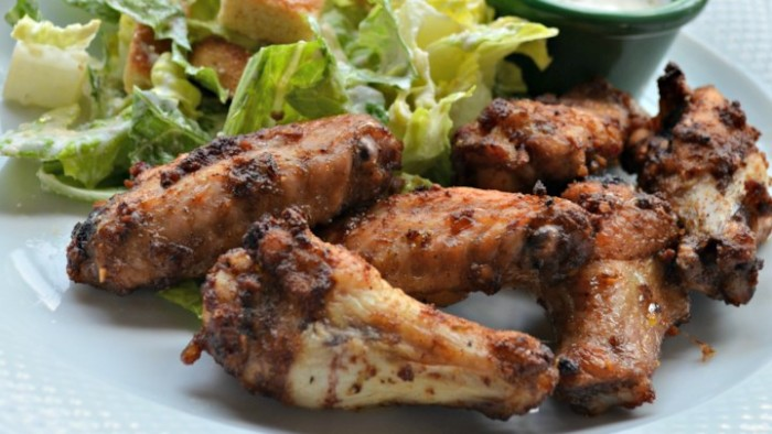 buffalo wings seen in close up, hour derves, next to a side of green salad, and a small dish with dip