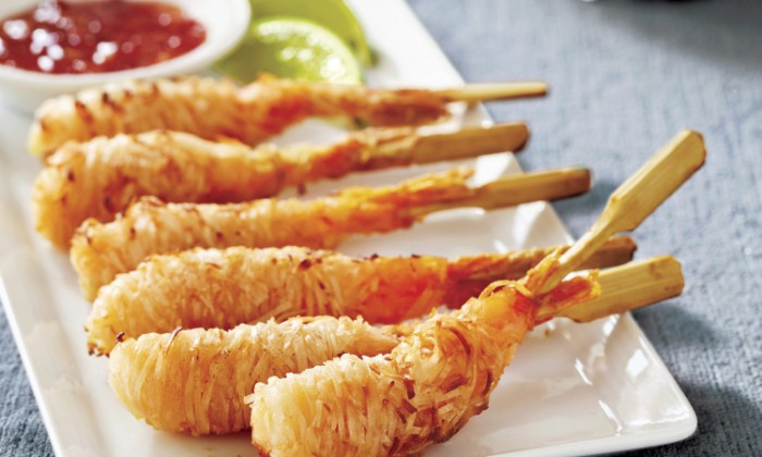 crispy prawns wrapped in noodles, amd served with a red dip, and two lime wedges, chinese cuisine-inspired appetizer