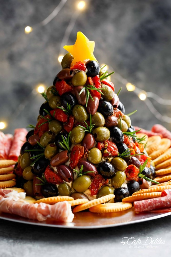 olives stacked in the shape of a christmas tree, and topped with a yellow star, hor d oeuvres ideas, on a plate with crackers and salami