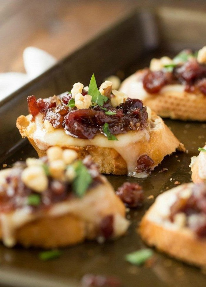 metal baking tray, containing several pieces, of grilled cheese bruschetta, topped with cranberry confit, and fresh basil